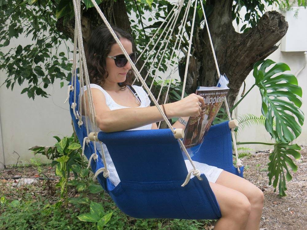 Blue Padded Hammock Chair With Wooden Arm Rests And Girl