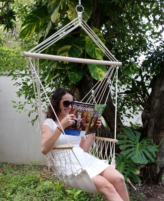 White Padded Hammock Chair With Wooden Arm Rests With Woman